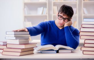 An overworked student with a large pile of books