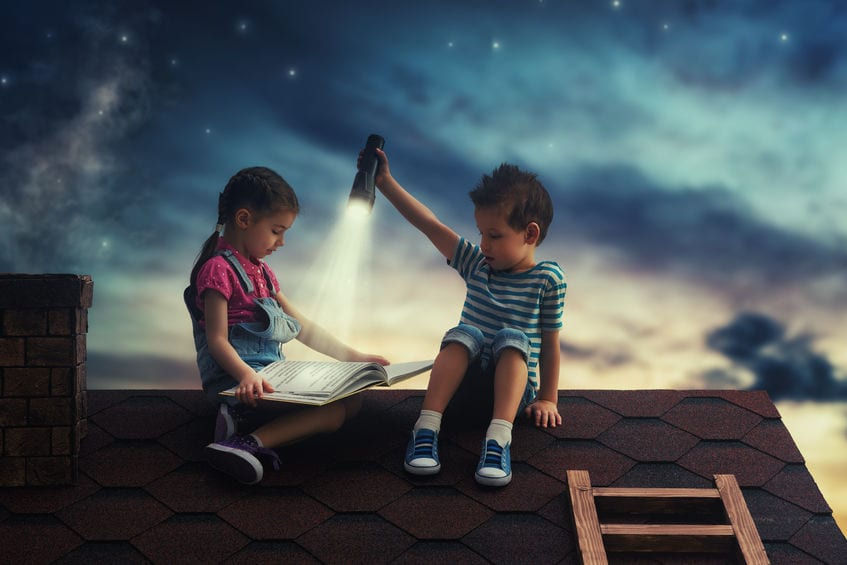 Children reading a story on a roof