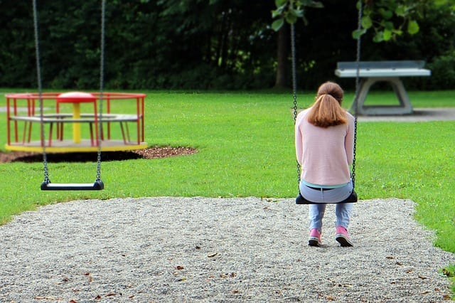 A downcast teacher sits alone on a swing pgce