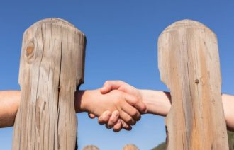 Two people shake hands through holes in a fence